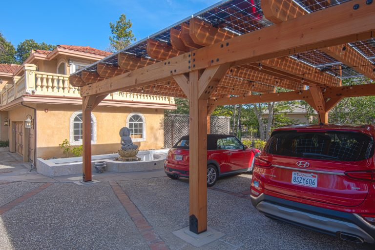 View of a solar carport outside of a home in Saratoga with view under the bifacial solar panels