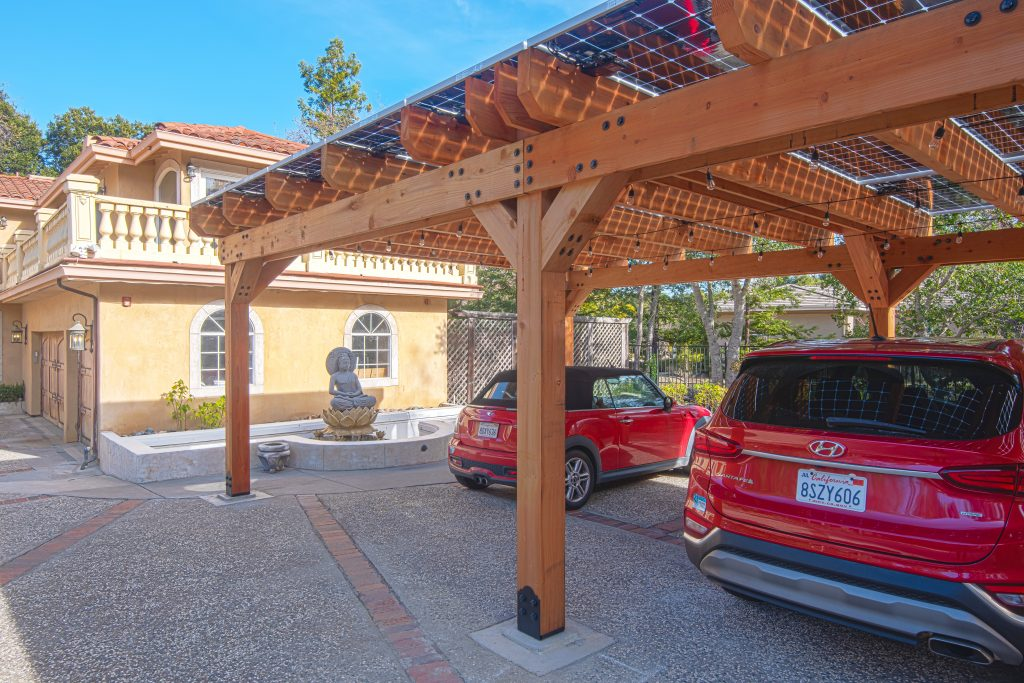 Solar carport installation showing the bifacial solar panels and cars parked underneath